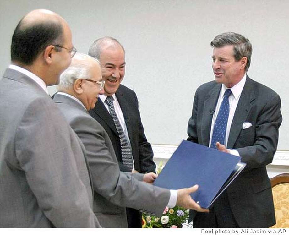 ALTERNATIVE CROP FROM BAG107 - U.S. administrator L. Paul Bremer, right, hands a document to Iraq's Chief Justice Midhat al-Mahmoudi, 2nd left, flanked by Iraqi Prime Minister Iyad Allawi, center, and Iraqi Deputy Prime Minister Dr. Barham Salih, left, sealing the transfer of sovereignty to Iraq during a ceremony in Baghdad, Iraq, Monday June 28, 2004. (AP Photo/Ali Jasim/Pool) Photo: ALI JASIM