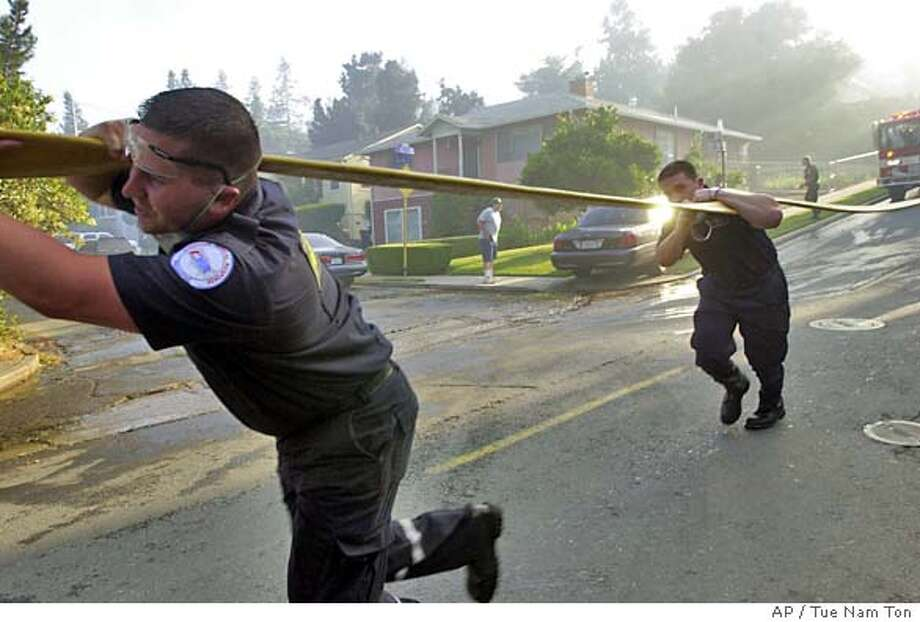 Firefighters and paramedics pull hoses through a neighborhood as they work to put out a fire that burned at least 250 acres in Martinez, Calif., on Friday, June 25, 2004. Two houses were destroyed in two separate fires. (AP Photo/Contra Costa Times, Tue Nam Ton) Photo: TUE NAM TON