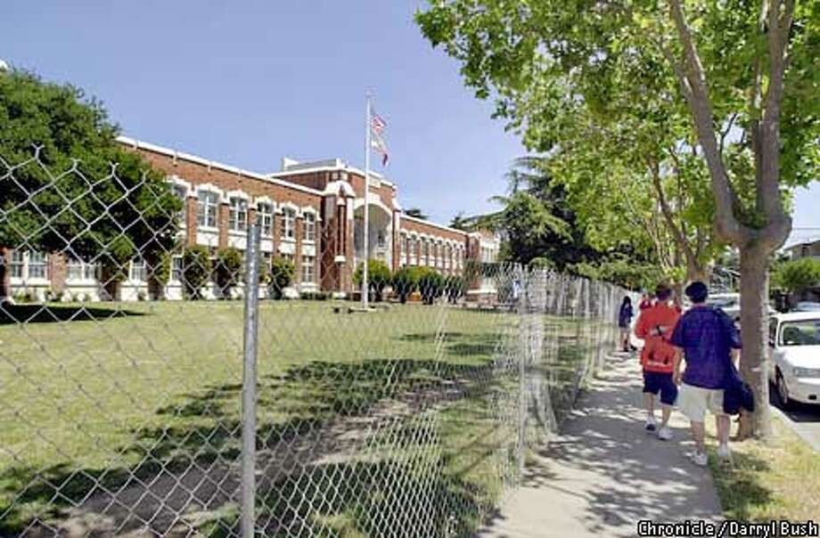 San Mateo High School students walk in front of their high school which is now fenced in and closed due to seismic safety problems, Monday afternoon. The students now go to school at San Mateo Performing Arts Center which is next door. Chronicle Photo by Darryl Bush Photo: DARRYL BUSH