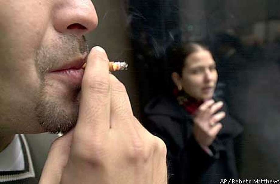 Office workers take a cigarette break at the entrance of their workplace in New York, Wednesday Dec. 11, 2002. New York City leaders have agreed to a sweeping ban on smoking in workplaces, including bars and restaurants, Mayor Michael Bloomberg said Wednesday. (AP Photo/Bebeto Matthews) Photo: BEBETO MATTHEWS