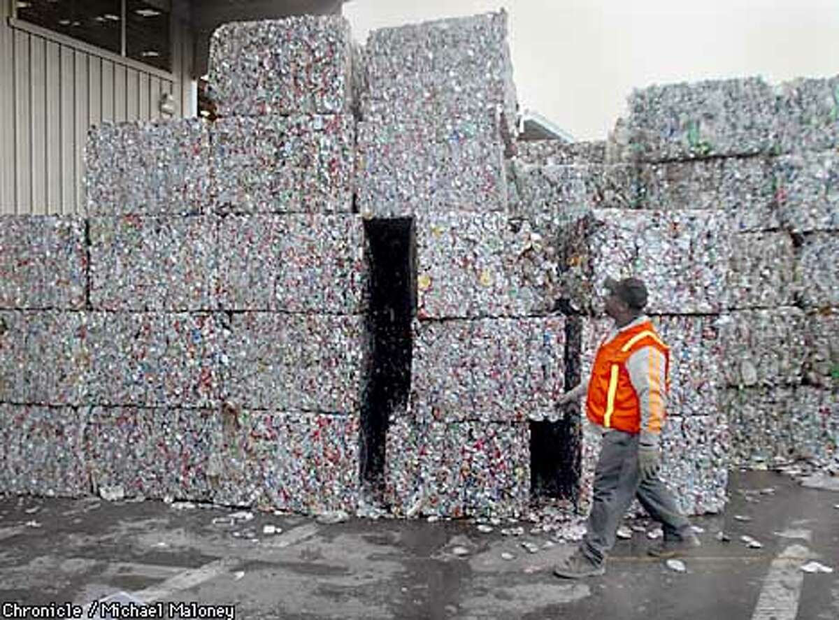 Dennis Davis walks past 1,000 lb bales of aluminum that are stacked waiting to be shipped out from the recycling center. On Thursday, SF announces it has reached the state-mandated goal of recycling 50% of it's waste. We look at the SF recycling center at Pier 96 to see how the material is separated. CHRONICLE PHOTO BY MICHAEL