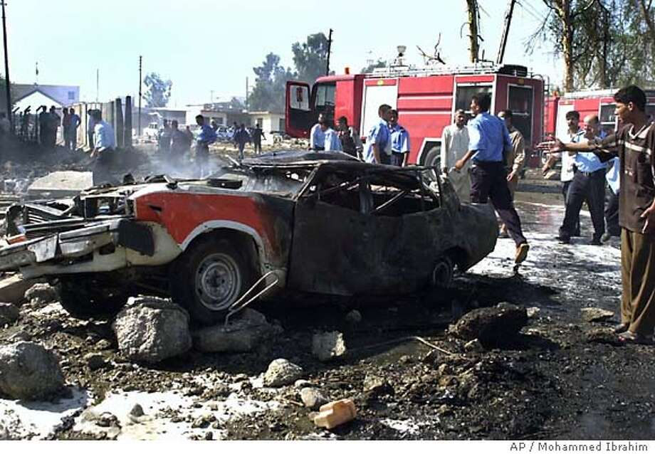 Iraqi police and medics rush to the scene of a car bomb explosion in Mosul, Iraq, Thursday June 24, 2004. A hospital official in Mosul said at least 50 people died in four bombings in the northern Iraqi city. (AP Photo/Mohammed Ibrahim) Photo: MOHAMMED IBRAHIM