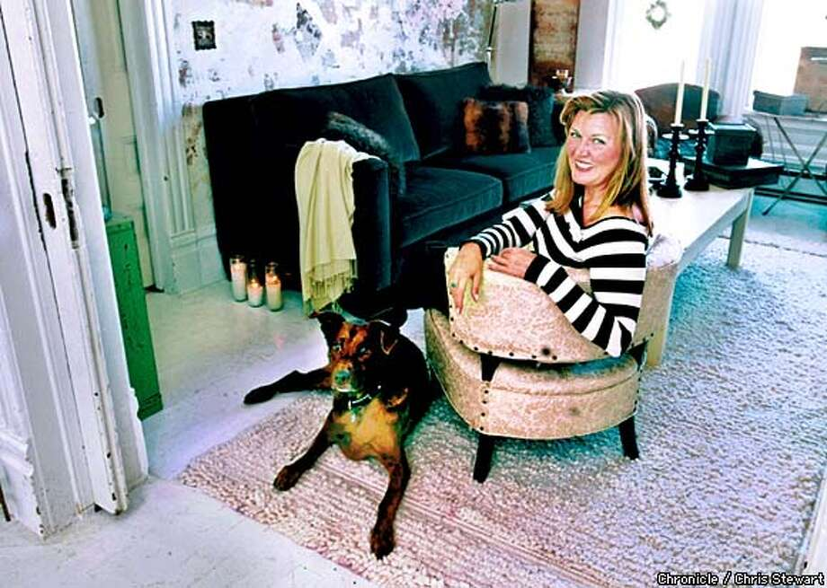 With her dog Jasper beside her, designer and retailer Pamela Fritz relaxes in a 1940s vintage brocade chair in her Hayes Street living room. Chronicle photo by Chris Stewart