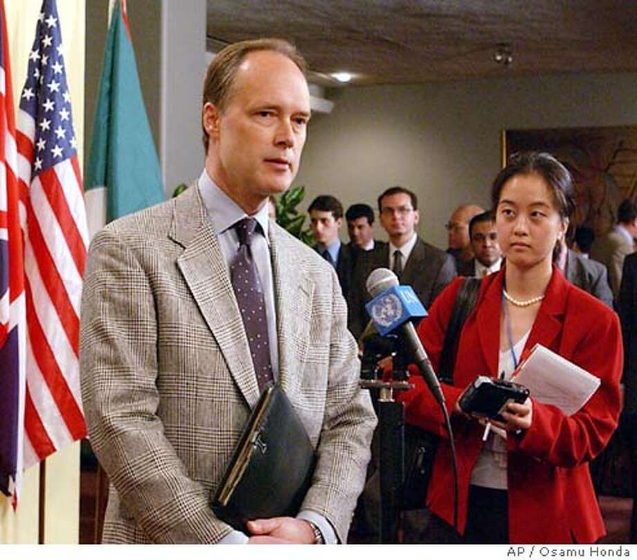 James Cunningham, U.S. deputy ambassador to the U.N., left, speaks to the media outside the Security Council Chamber at the United Nations headquarters in New York, Wednesday, June 23, 2004. Facing strong opposition, the United States announced Wednesday it was dropping a resolution seeking to renew the exemption for American peacekeepers from international prosecution for war crimes. Woman on the right is an unidentifed U.S. diplomat. (AP Photo/Osamu Honda) Photo: OSAMU HONDA