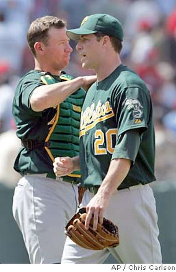 Oakland Athletics starting pitcher Mark Mulder, right, gets a pat on the back from catcher Damian Miller during their 2-1 win over the Anaheim Angels at Angel Stadium in Anaheim, Calif., Thursday, June 24, 2004. Mulder (9-2) pitched his major league-leading fourth complete game, allowing four hits while striking out four and walking three. (AP Photo/Chris Carlson) Photo: CHRIS CARLSON