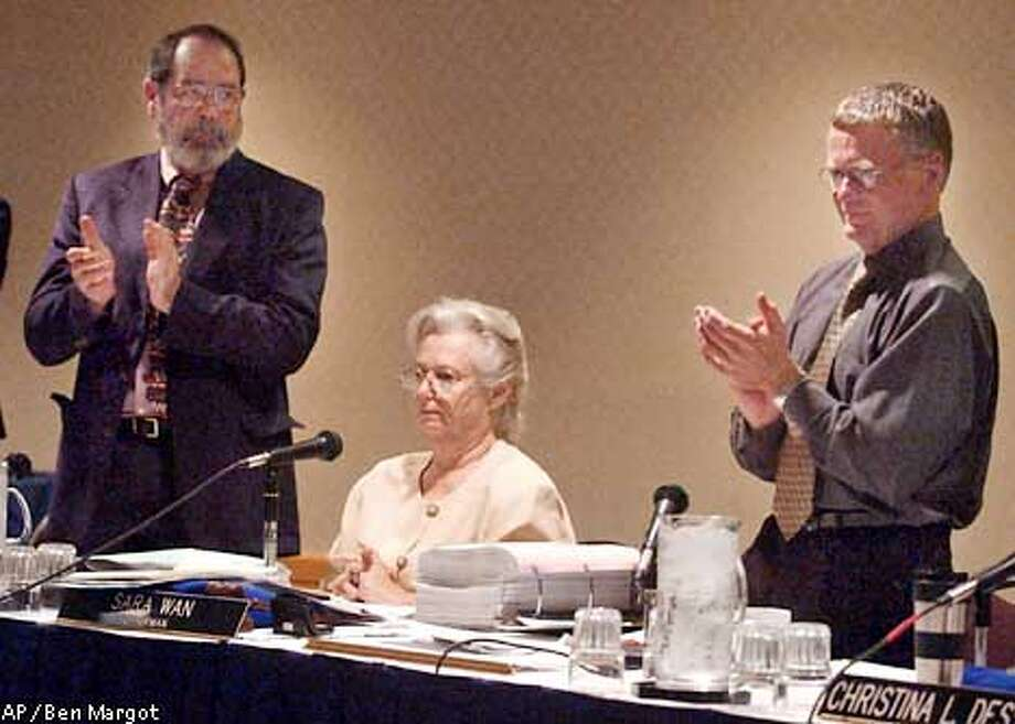 California Coastal Commissioners Mike Reilly, left, and Dave Potter applaud Chairwoman Sara Wan, seated center, during a meeting Wednesday, Dec. 11, 2002, in San Francisco. The California deadlocked Wednesday morning in a vote to select a new leader, stalling a move that some feared could tilt the powerful panel away from coastal protection. The vote came after preservation activist Sara Wan, the current chairwoman, decided to pull her name from consideration. Her decision left contractor and Monterey County supervisor Potter and longtime commissioner Reilly bidding for the influential post. The board split six-to-six on two separate votes, leaving Wan as chairwoman until another vote can be held at January's meeting. (AP Photo/Ben Margot) Photo: BEN MARGOT