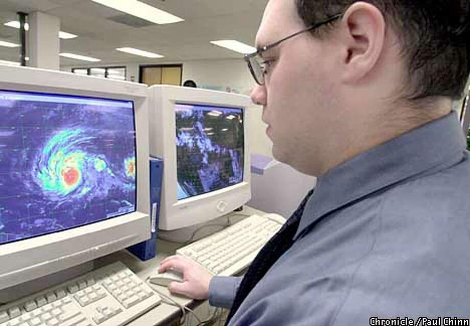Meteorolgist Jim Laurie monitors Typhoon Pongsona which is spinning over the south Pacific Ocean. Weathernews monitors worldwide weather and ocean conditions and relays the information to ships traversing the oceans.  PAUL CHINN/S.F. CHRONICLE Photo: PAUL CHINN