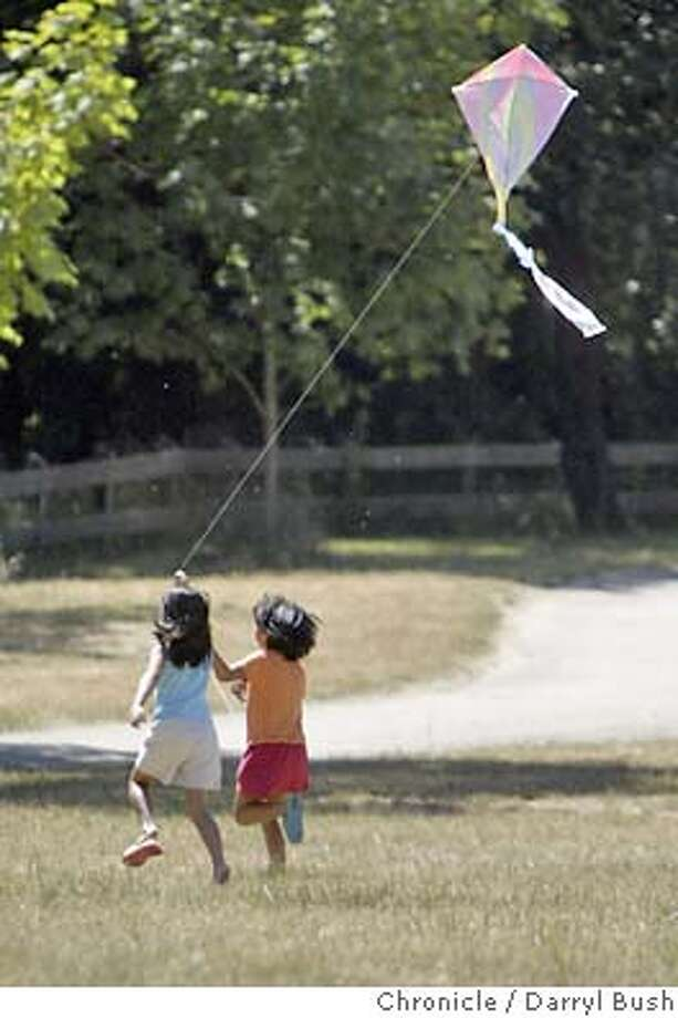 Rebecca Depadua, 6, right, and cousin Michelle Depadua, 8, left, fly a kite with Rebecca's father, Noli Depadua, all from Oakland, in the Redwood Regional Park of East Bay Regional Park District.  Event on 6/23/04 in Oakland.  Darryl Bush / The Chronicle Photo: Darryl Bush