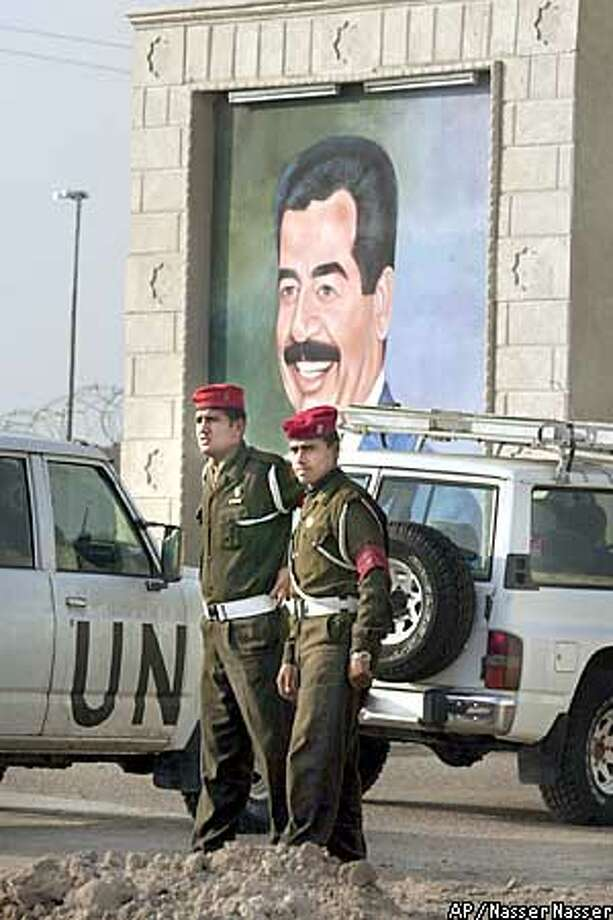 Two Iraqi soldiers stand guard as U.N. weapons inspectors vehicles drive by a portrait of Iraqi President Saddam Hussein as they enter the Iraqi Nuclear Energy Organization facility in Tuwaitha some 25 kilometers (16 miles) south east of Baghdad Monday Dec. 9 , 2002. (AP Photo/Nasser Nasser) Photo: NASSER NASSER