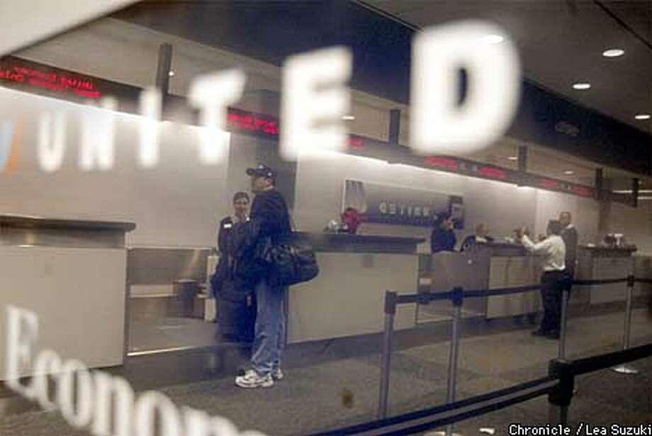 Counter person's assist passengers on Sunday night at SFO. Photo By Lea Suzuki
