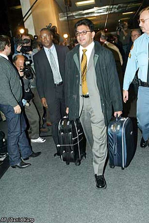 Legal Officer Surya Sinha of UNMOVIC enters the United Nations Headquarters with two suitcases of documents from Iraq, Sunday, Dec. 8, 2002. (AP Photo/David Karp) Photo: DAVID KARP