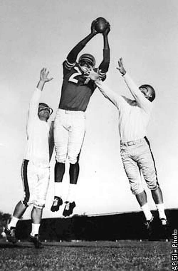 SPECIAL TO SAN FRANCISCO CHRONICLE--R.C. Owens, the San Francisco 49ers fabulous pass-cathcer demonstrates his famous alley-oop catch for the camer during workout at Redwood City, Calif. Nov.7, 1957. Acting as defensive men against the pass are Rul Carr, left, and Dicky Moegle, two aces in that department. Three times in 1957 Owens came up wityh the catch to win games --the last time against Detroit in the final 11 seconds of play. Owens was a former Idaho basketball star. (AP photo/stf/rh)
