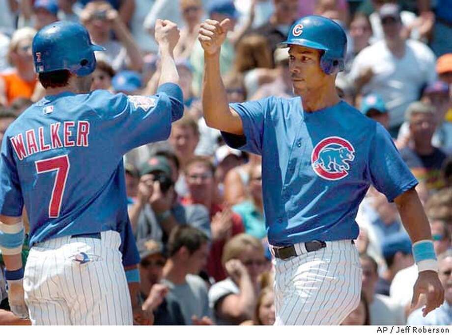 Chicago Cubs' Moises Alou, right, is congratulated by teammate Todd Walker (7) after driving in Walker on a home run during the first inning against the Oakland Athletics Sunday, June 20, 2004 in Chicago. (AP Photo/Jeff Roberson) Photo: JEFF ROBERSON