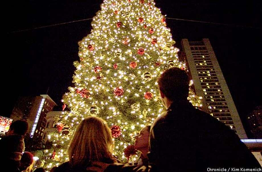 The glowing 80-foot Christmas tree towers over visitors at San Francisco's Union Square. Chronicle photo by Kim Komenich