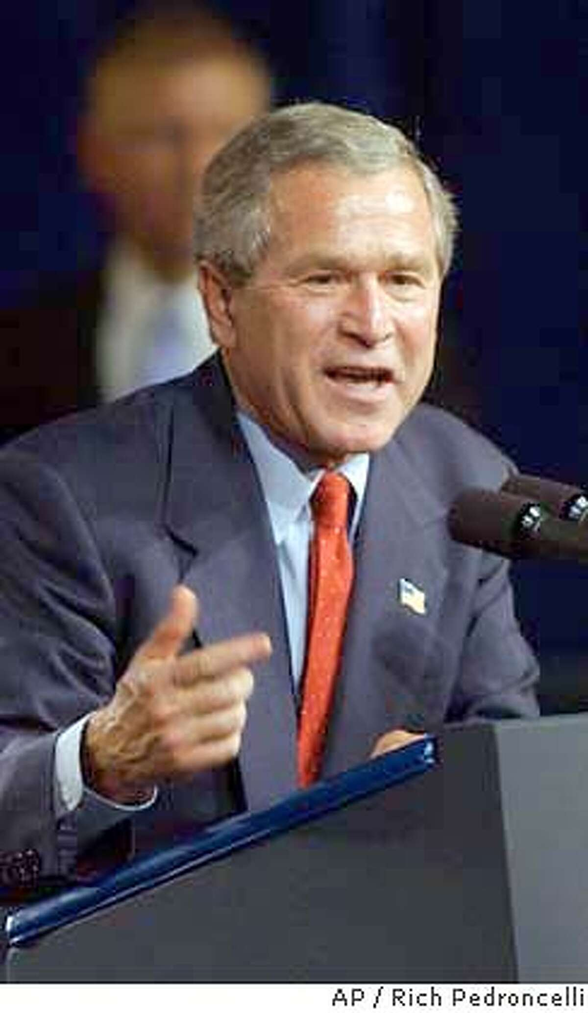 President Bush gestures as he addresses a crowd of nearly 10,000 people who attended a campaign rally at the Reno-Sparks Convention center in Reno, Nev., Friday, June 18, 2004. This was the third stop on a two-day swing through western states for the President. (AP Photo/Rich Pedroncelli)