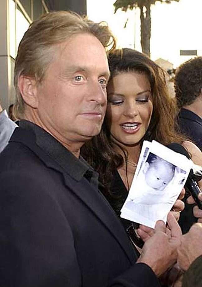 Michael Douglas, Catherine Zeta-Jones and photo of daughter Carys Photo: AP