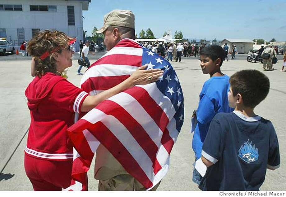 Sgt. Frederico Viscarra wears an American flag as he is greetd by his sister Diana Martinez and his two sons, Matthew, 11 and Christopher, 8, they are from Dinuba, Ca. Soldiers frrom the 341st Military Police Unit out of San Jose returned home today after more than 16 months of service, with more than a year in Kuwait and Iraq. event on 6/19/04 in Mountain View Michael Macor/San Francisco Chronicle Photo: Michael Macor