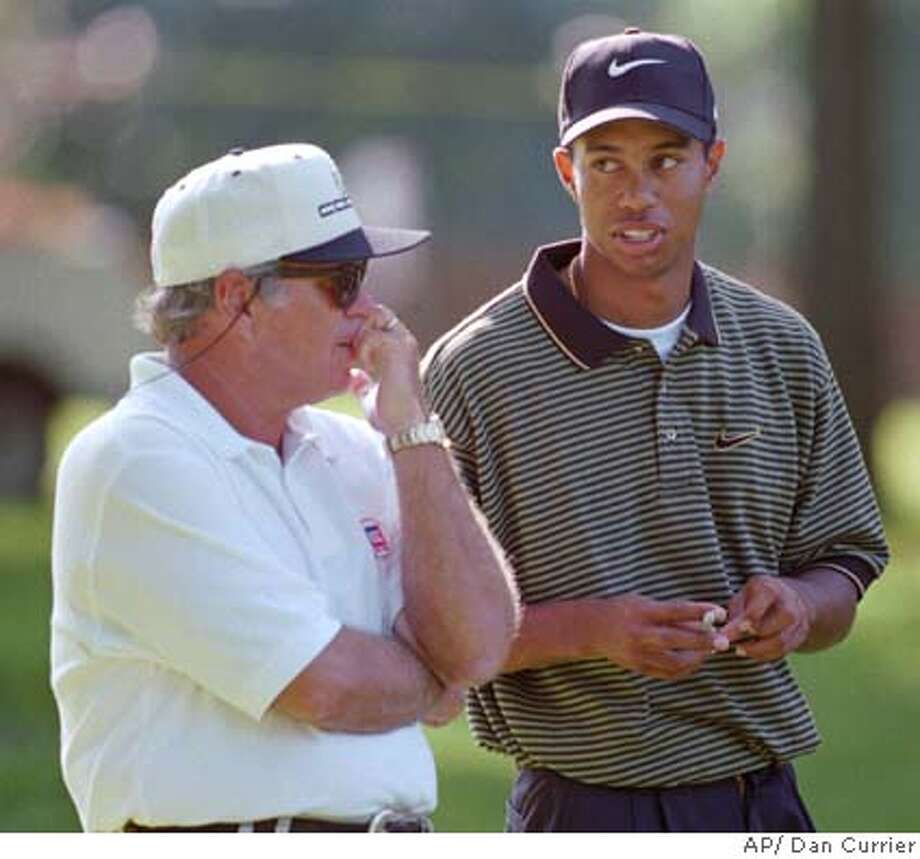 Tiger Woods talks with his swing instructor, Butch Harmon, left, during a break in the pro-am of the Greater Milwaukee Open on Wednesday, Aug. 28, 1996, at the Brown Deer Golf Course in Milwaukee. Woods, who won his third consecutive U.S. Amatuer title last Sunday, announced Tuesday, Aug. 27 that he was turning professional. (AP Photo/Dan Currier) Photo: DAN CURRIER