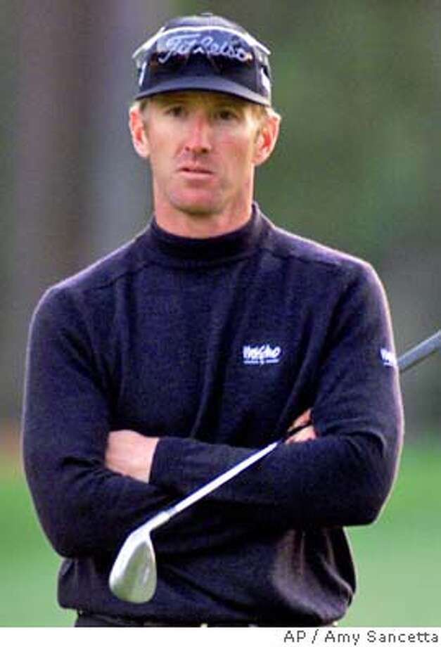 FILE -- David Duval, from Ponte Vedra Beach, Fla., tries to stay warm on the 15th hole just before play is suspened during third round play of the Masters at the Augusta National Golf Club in Augusta, Ga., in this April 8, 2000 photo. Duval withdrew from The International on Thursday August 3, 2000 because of a back injury that has been bothering him since the British Open. (AP Photo/Amy Sancetta) DIGITAL IMAGE Photo: AMY SANCETTA