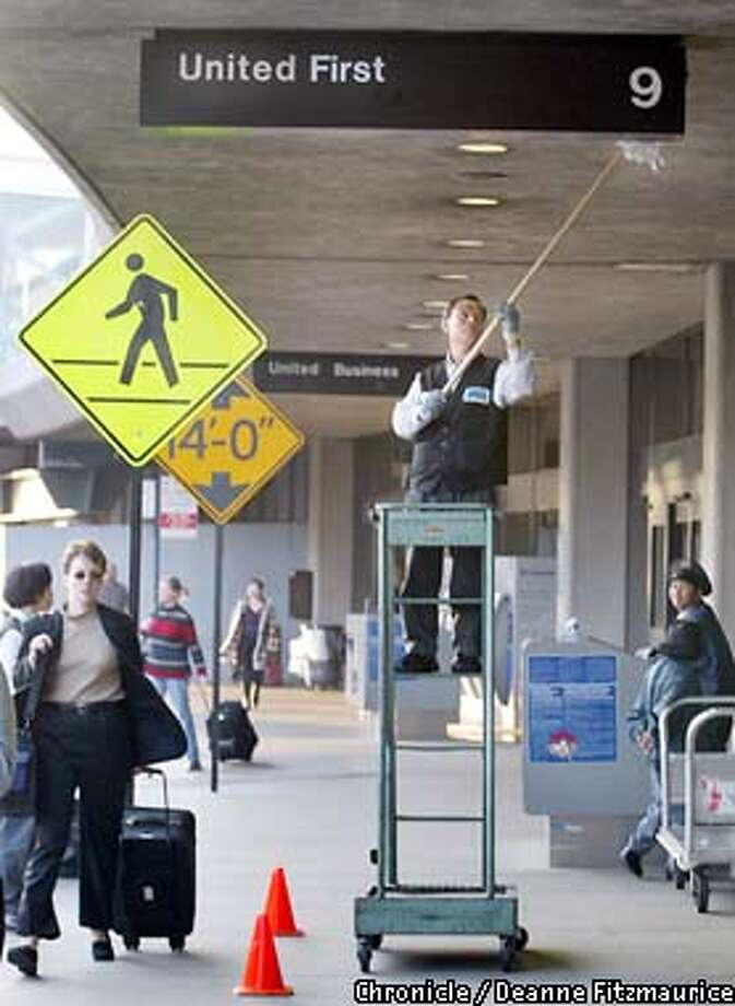 Peter Lee cleans signs at United Airlines at SFO. The federal government today decided not to entend the $1.8 billion loan guarantee which leaves United Airlines that much closer to bankrupcy. CHRONICLE PHOTO BY DEANNE FITZMAURICE Photo: DEANNE FITZMAURICE