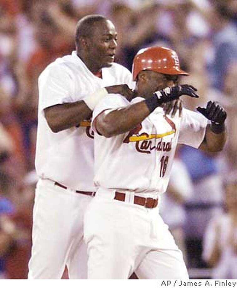 St. Louis Cardinals Edgar Renteria, left, and Reggie Sanders celebrate following Sanders walk off single in the ninth inning to defeat the Oakland Athletics in their Interleague baseball game in St. Louis June 17, 2004. The Cardinals defeated the Athletics by the final score of 5-4. (AP Photo/James A. Finley) Photo: JAMES A. FINLEY