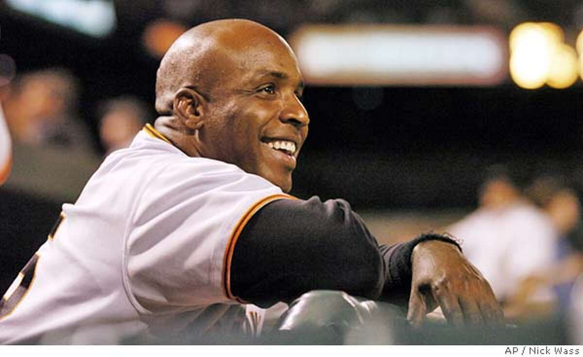 San Francisco Giants' Barry Bonds smiles during a break in the action against the Baltimore Orioles, during the 11th inning of the Orioles' 5-4, 12-inning win early Sunday, June 13, 2004, at Camden Yards in Baltimore.(AP Photo/Nick Wass)