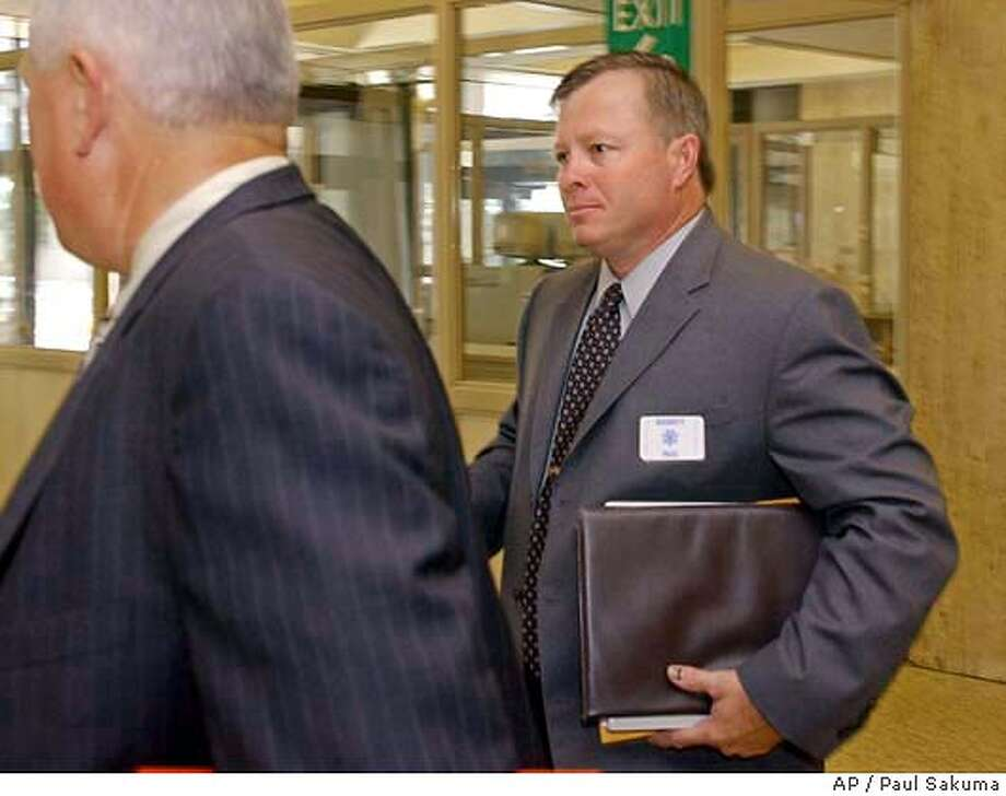 Modesto Police Sgt. Timothy Helton, right, is escorted into a Redwood City, Calif., courtroom before he testified in the Scott Peterson trial, Wednesday, June 16, 2004. Peterson is the Modesto, Calif., man who could face the death penalty if he's convicted of two counts of murder forthe deaths of his wife, Laci Peterson, and their unborn son. Helton helped in the search for Laci Peterson. (AP Photo/Paul Sakuma) Photo: PAUL SAKUMA