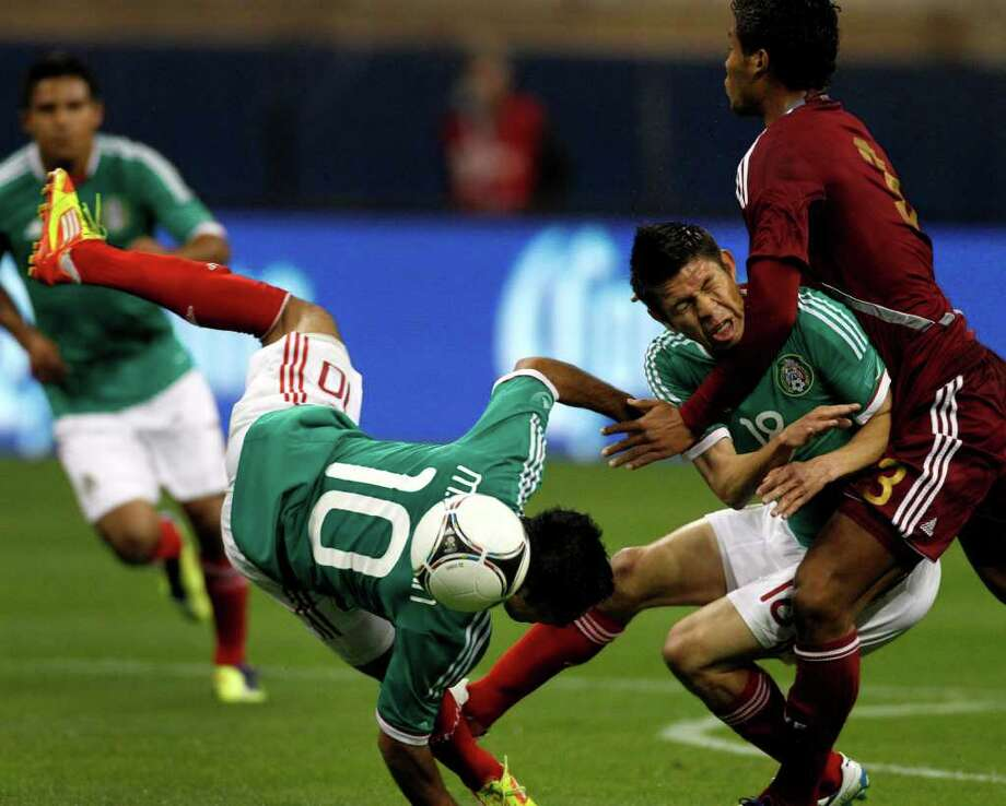 Mexico's Marcos Fabian (10) and Oribe Peralta (18) clash with Venezuela's Carlos Salazar, right, in what was supposed to be a friendly match. Photo: Brett Coomer / © 2012 Houston Chronicle