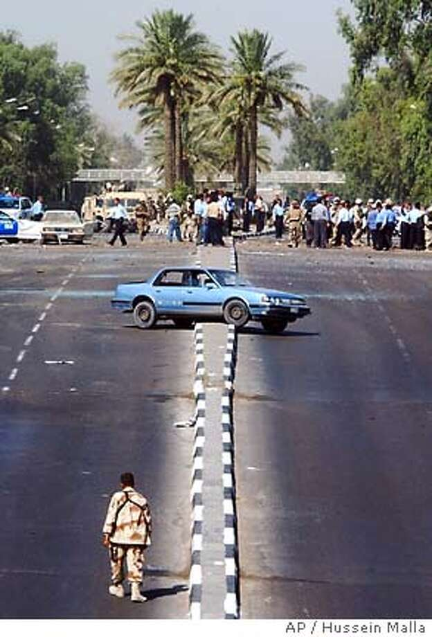 A car, which was thrown into middle of the road by the force of a blast, sits in the street while U.S. and Iraqi troops and Iraqi police secure the scene of an explosion in central Baghdad, Iraq Thursday June 17, 2004. At least 21 people were killed and 69 wounded by what is believed to have been a car bomb outside a recruiting station for Iraqi security forces, police said. (AP Photo/Hussein Malla) Photo: HUSSEIN MALLA