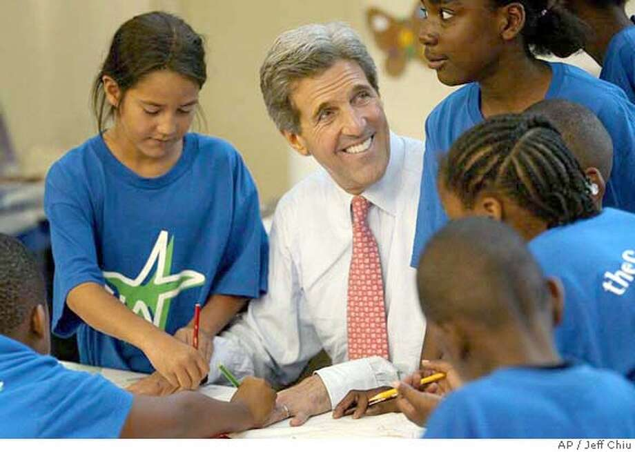 Democratic presidential candidate Sen. John Kerry, D-Mass., smiles as he has his hands traced by students at an afterschool program at Marion Franklin Community Recreation Center in Columbus, Ohio, on Wednesday, June 16, 2004. (AP Photo/Jeff Chiu) Photo: JEFF CHIU