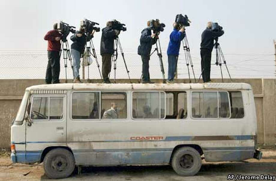 Television cameramen stand on a bus parked outside the Karama factory as they try to get a view of U.N. weapons inspectors visiting the facility which once made parts for now-banned missiles in Baghdad, Monday, Dec. 2, 2002. Iraq modified Soviet-made Scuds to longer range and used them in the Persian Gulf War. Iraq is prohibited from having such missiles--which have a range of 400 miles--and inspectors presumably wanted to ensure that such work has not resumed.(AP Photo/Jerome Delay) Photo: JEROME DELAY