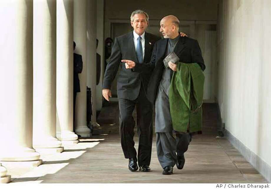 President Bush, left, and Afghanistan's President Hamid Karzai walk together along the Collonade to a working lunch after speaking with reporters in the Rose Garden in at the White House Tuesday, June 15, 2004 in Washington. (AP Photo/Charles Dharapak) Photo: CHARLES DHARAPAK