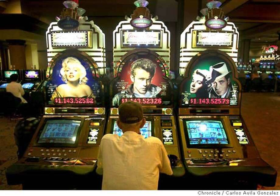 A guest tries his luck at a bank of slot machines at the Jackson Rancheria Casino outside Jackson, Ca., on Thursday, June 3, 2004. The town of Jackson, a small, bucolic community in the foothills of the Gold Country, has benefitted from the Jackson Rancheria Casino just outside of town which bolsters tourism and provides money to the town and county. The casino has come a long way from the metal building that it once used to be, now including a hotel, and several casino buildings. Fortunately for Jackson and Amador County, the Jackson Rancheria band of the Miwuk tribe is sharing in the wealth, contributing for such things as increased police resources and offsetting such things as county expenses for prosecution of drug convictions that are up dramatically in the area. For most residents of the town, the casino and the tribe that run it, are good neighbors. Photo taken on 06/03/04 in Jackson, Ca. Photo By Carlos Avila Gonzalez / The San Francisco Chronicle Photo: Carlos Avila Gonzalez SFChron