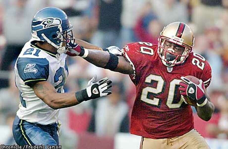49ERS5-C-01DEC02-SP-FRL: Garrison Hearst stiff arms Ken Lucas and beat him for a large gain in the 3rd quarter. 49ers beat Seattle Seahawks at Candlestick Park SF 31-24. Chronicle photo by Frederic Larson Photo: FREDERIC LARSON