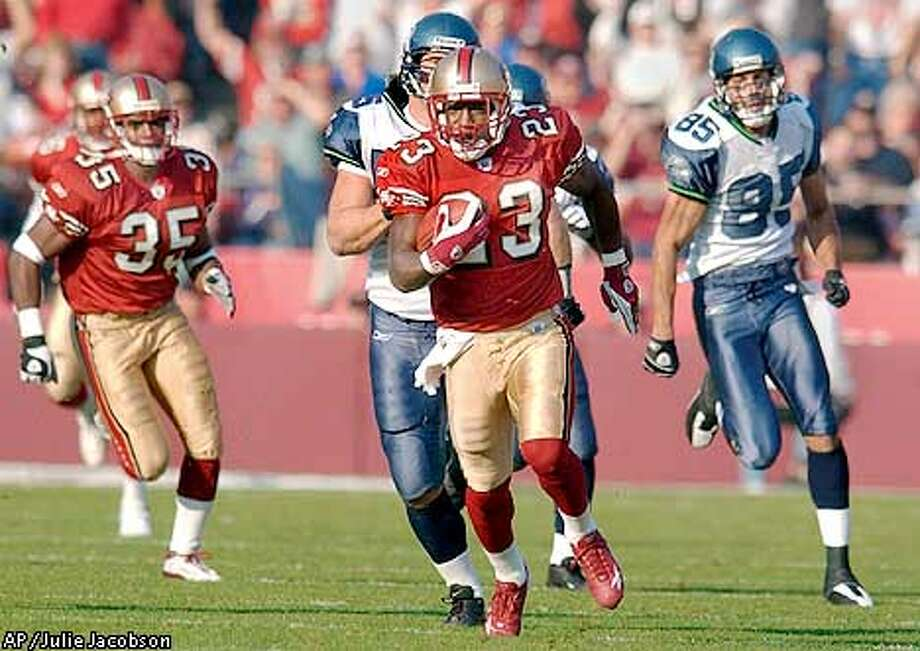 San Francisco 49ers punt returner Jimmy Williams (23) beats the defense of Seattle Seahawks Marcus Bell, rear center, and Alex Bannister (85) to return the ball 89 yards for a touchdown as teammate Jason Moore (35) follows behind during the second quarter Sunday, Dec. 1, 2002 in San Francisco. (AP Photo/Julie Jacobson) Photo: JULIE JACOBSON