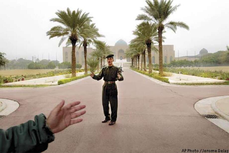 An Iraqi presidential guard waves at journalists to leave the premises after they were allowed in following a United Nations weapons inspectors' visit in the Al-Sajoud palace, one of Saddam Hussein's presidential palaces along the Tigris River, in Baghdad Tuesday, Dec. 3, 2002. Access to such sites was an explosive issue in the previous round of inspections in the 1990s. (AP Photo / Jerome Delay) Photo: JEROME DELAY