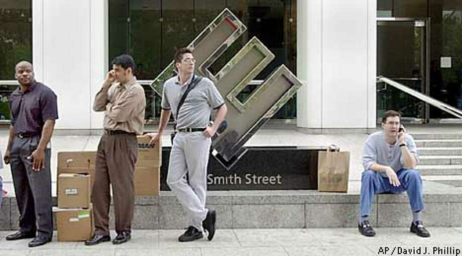 Enron employees sit outside the company's headquarters with their boxes Monday, Dec. 3, 2001, in Houston. Enron filed for Chapter 11 protection and sued rival Dynegy Inc. for $10 billion as it tries to reverse a tailspin that has crippled the one-time energy giant. In the meantime, the company said an undetermined number of its 21,000 workers, mostly among the 7,500 in Houston, would be laid off. (AP Photo/David J. Phillip) Photo: DAVID J. PHILLIP