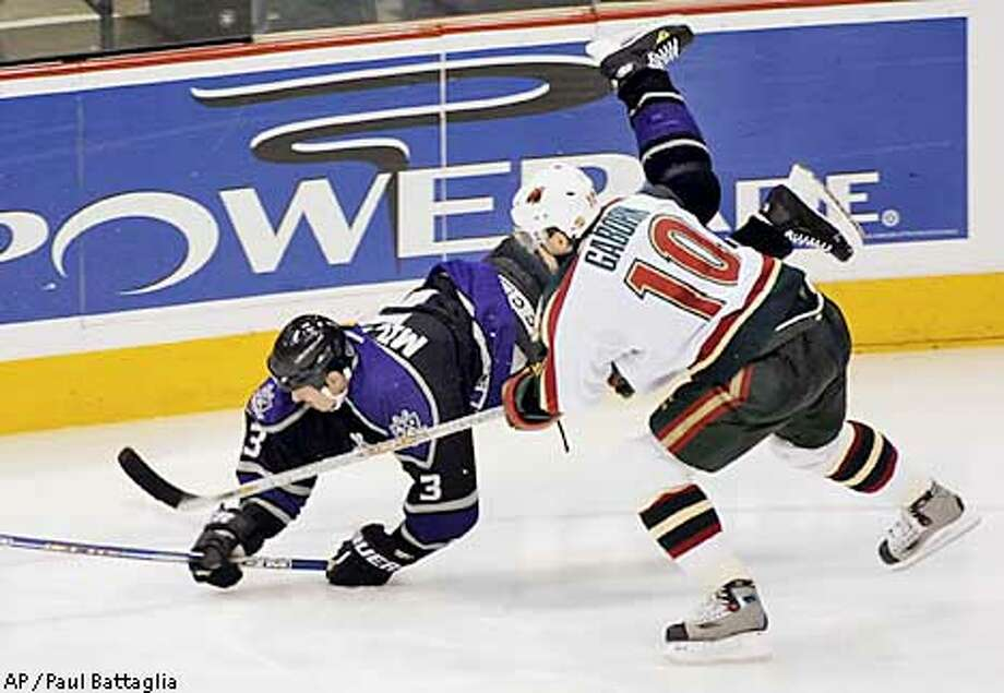 Los Angeles Kings' Aaron Miller (3) is upended by Minnesota Wild right wing Marian Gaborik (10) as they go after the puck during the third period Tuesday, Nov.19, 2002, in St. Paul, Minn. The game ended in a 2-2 tie. (AP Photo/Paul Battaglia) Photo: PAUL BATTAGLIA