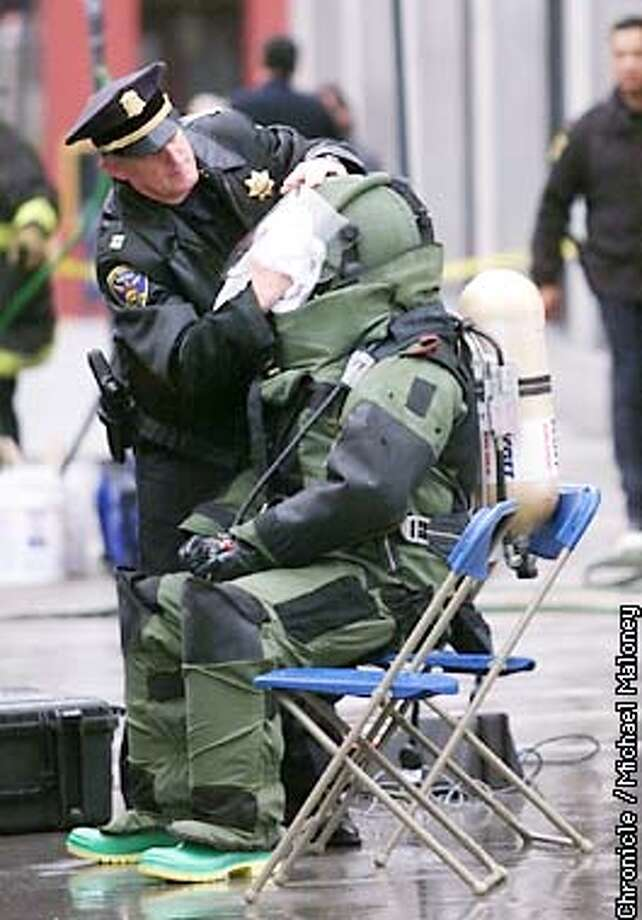 Captain Alex Fagan wipes the rain off bomb squad member Dino Zografos' face mask. Zografos (cq) and his partner Michael Travis suited up to xray the suspicious package.  A suspicious package was sent to the Federal Building in SF so the bomb squad was sent out to xray it.  CHRONICLE PHOTO BY MICHAEL MALONEY Photo: MICHAEL MALONEY