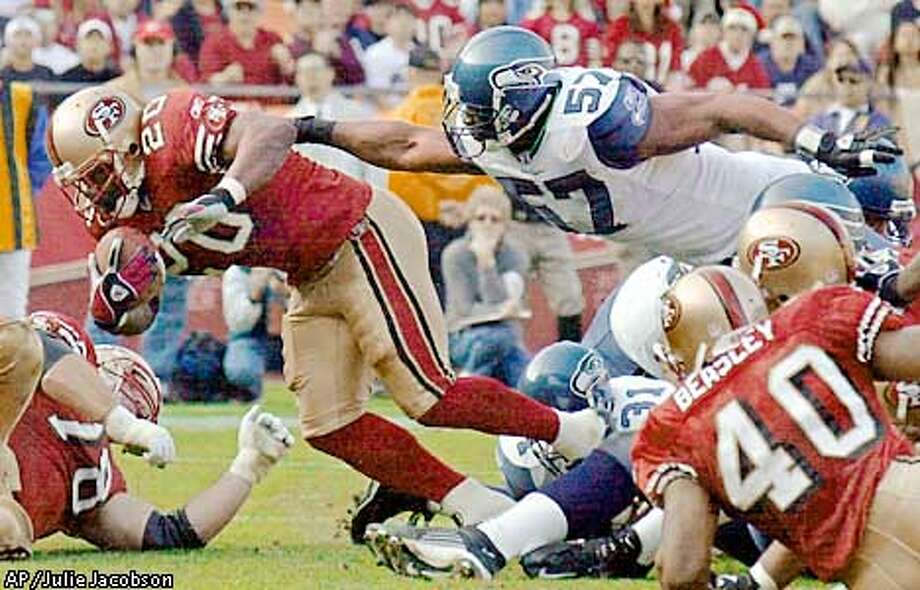 San Francisco 49ers running back Garrison Hearst (20) lunges over the goal line and out of the reach of Seattle Seahawks linebacker Orlando Huff for a second quarter touchdown Sunday, Dec. 1, 2002 in San Francisco. (AP Photo/Julie Jacobson) Photo: JULIE JACOBSON
