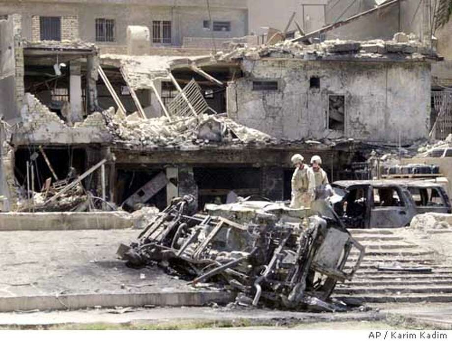 U.S. Army soldiers look over the aftermath following a car bombing in central Baghdad, Iraq, Monday, June 14, 2004. (AP Photo/Karim Kadim) Photo: KARIM KADIM
