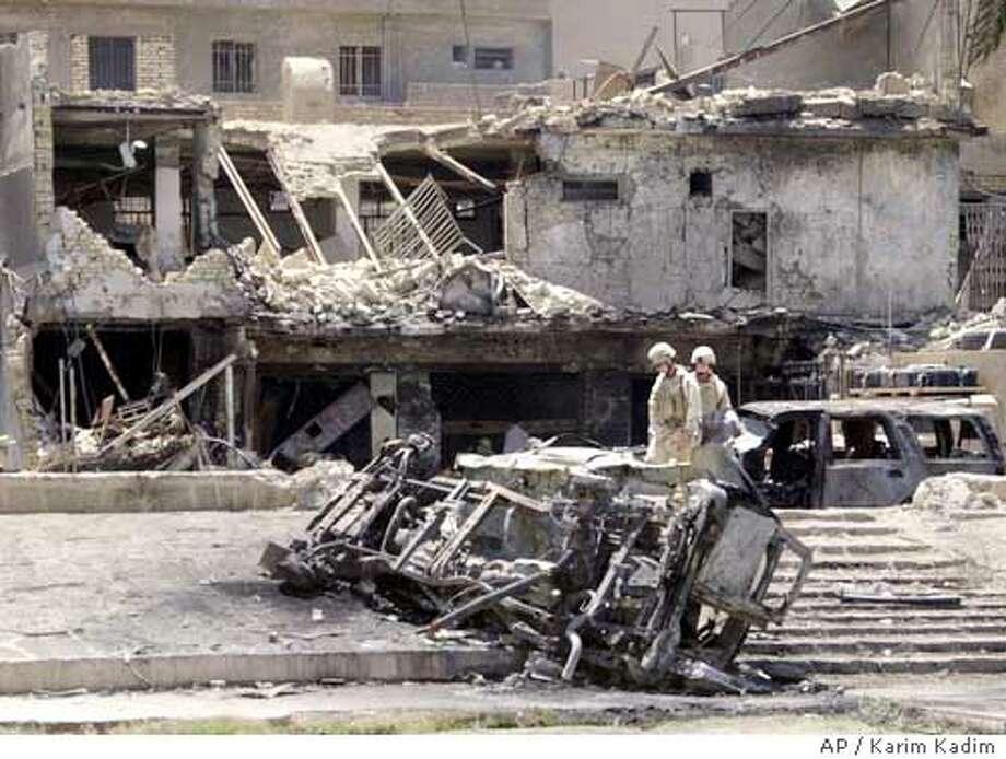 U.S. Army soldiers look over the aftermath following a car bombing in central Baghdad, Iraq, Monday, June 14, 2004. (AP Photo/Karim Kadim) Photo: KARIM KADIM