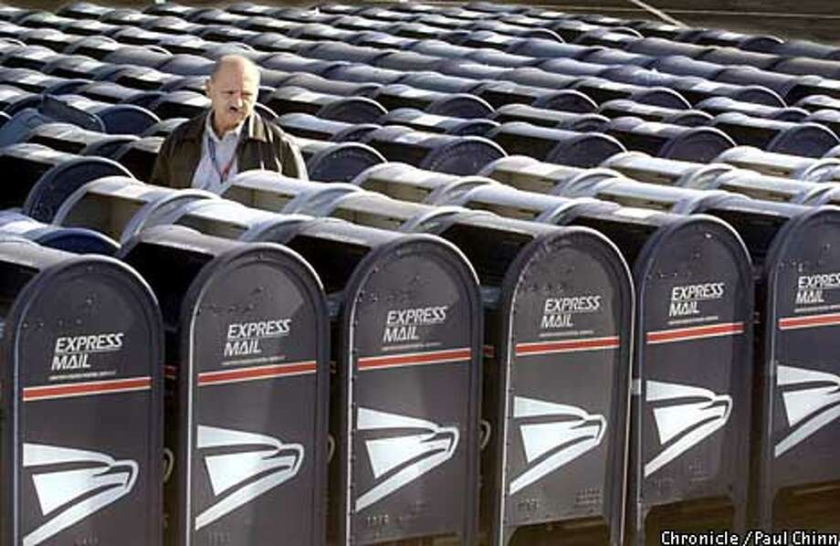 "Gus Ruiz, from the Postal Service, inspects roughly 150 mailboxes taken out of circulation that are lined up in a ""graveyard"" behind a San Jose Post Office.  PAUL CHINN/S.F. CHRONICLE Photo: PAUL CHINN"