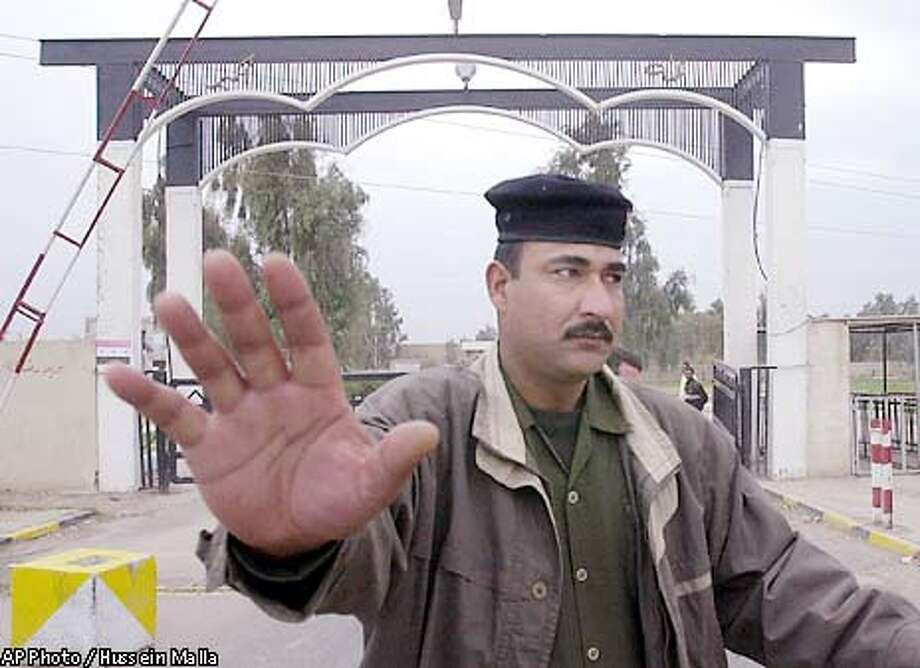 An Iraqi solodier prevents photographers and cameracrews from taking pictures of a military production facility at Umm al-Maarek or mother of all battles complex 20 kilometers (12 miles) southeast of Baghdad, Iraq, on Saturday Nov. 30, 2002. (AP Photo/Hussein Malla) Photo: HUSSEIN MALLA