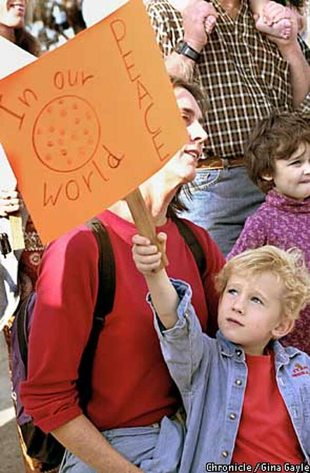 Quinn Folks,5, holds a peace sign while he and his mother Lorilyn Parmer-Folks listen to the Thanksgiving poem after the turkey shoot and peace march through Pt. Richond on Thanksgiving Day. Photo by Gina Gayle/The SF Chronicle. Photo: GINA GAYLE