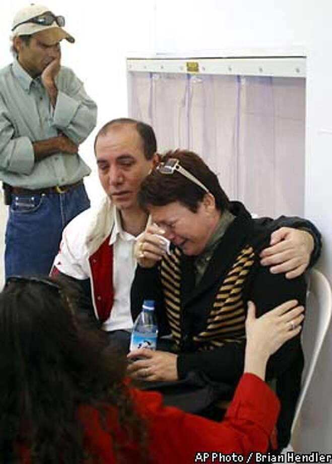 Miki Adler, right, the aunt of brothers Noy and Dvir Anter, ages 12 and 14, who were killed in the attack in Kenya, cries after a military plane carrying their bodies arrived at a military airport near Tel Aviv Friday, Nov. 29, 2002. An Israeli air force plane carrying eight Israelis wounded in a hotel bombing in Kenya landed in Israel on Friday, and several more rescue flights were to arrive later in the day. (AP Photo/Brian Hendler) Photo: BRIAN HENDLER