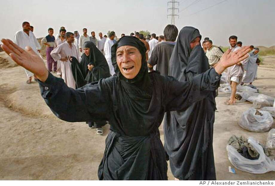 An Iraqi woman gestures as she cries walking along plastic bags containing remains of bodies pulled from a mass grave in Mahaweel, 60 miles south of Baghdad, central Iraq, Thursday, May 15, 2003. Villagers dug up the remains of more than 3,000 people they suspect were killed during the 1991 Shiite revolt against Saddam Hussein's regime. Uncounted bodies remained unearthed at the site. By every indication, the mass grave in Mahaweel is the largest found in Iraq since U.S. forces overthrew Saddam and hisBaath Party government last month. (AP Photo/Alexander Zemlianichenko) Photo: ALEXANDER ZEMLIANICHENKO
