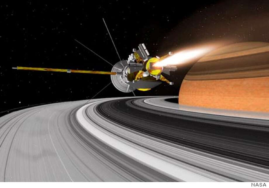 ** FILE ** In this artist's conception, NASA's $3.3 billion spacecraft, the Cassini Orbiter, nears the rings of Saturn. Cassini is nearing the end of it's seven-year voyage to Saturn, only to begin an intensive study of the second-largest planet, its rings and the stable of moons that orbit it. The spacecraft is on schedule to enter orbit around Saturn on June 30. (AP Photo/NASA, JPL, Space Science Institute)