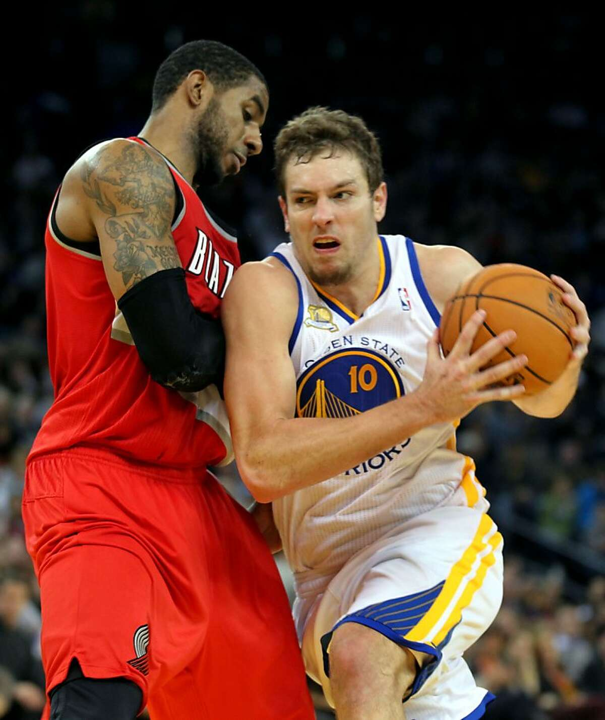 Golden State Warriors' Davis Lee (10) drives against Portland Trail Blazers Lamarcus Aldridge (12) during the second half of their NBA basketball game in Oakland, Calif., Wednesday, January 25, 2012.