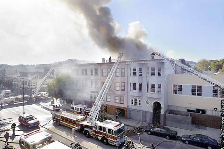FIRE4-C-26NOV02-MT-FRL: Two four story structures where engulfed in flames and smoke as fire fighters tackle the three alarm fire on Guerrero near 17th Street in San Francisco. Chronicle photo by Frederic Larson